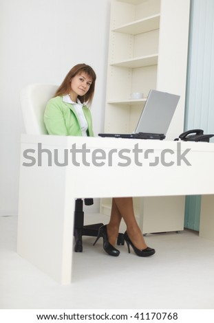 Businesswoman sits at a table at light office with the laptop