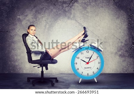 Businesswoman sits in chair, looking at camera. Put your feet up on big red alarm clock. Concrete background