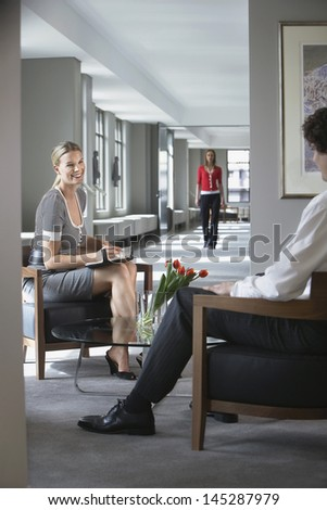 Businesswoman sitting and talking to cropped businessman in office - stock photo