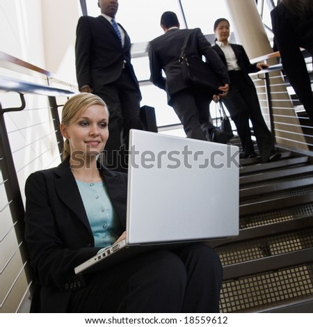 Businesswoman sitting and working on laptop on busy office stairs - stock photo