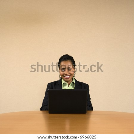 Businesswoman sitting at conference table smiling and typing on laptop computer. - stock photo