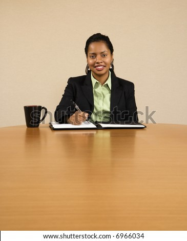 Businesswoman sitting at conference table smiling and writing in notebook. - stock photo