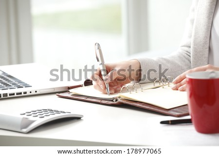 Businesswoman sitting at desk and makes a note in office. - stock photo