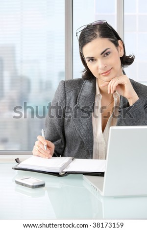 Businesswoman sitting at desk in front of offive windows, thinking over laptop computer and personal organizer.