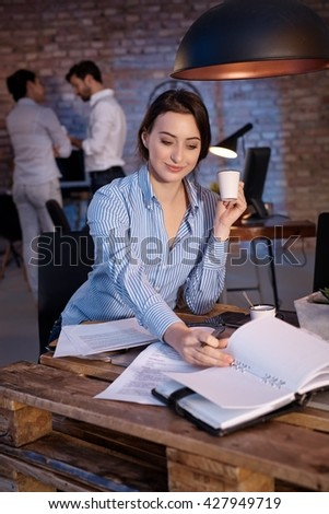 Businesswoman sitting at desk, working, drinking coffee. - stock photo