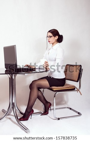 businesswoman sitting at desk working on a computer - stock photo