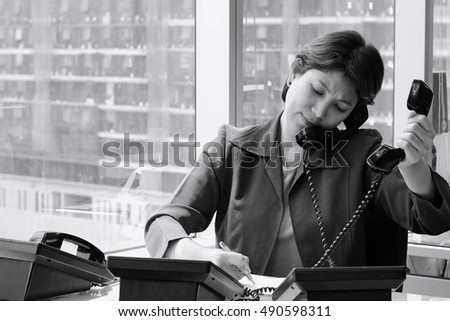 Businesswoman Sitting at her Desk Answering a Telephone Call from a Customer