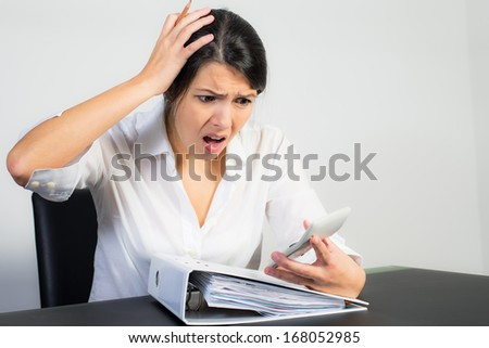 Businesswoman sitting at her desk with a large office binder looking at her calculator in horror or dismay with her mouth open in shock