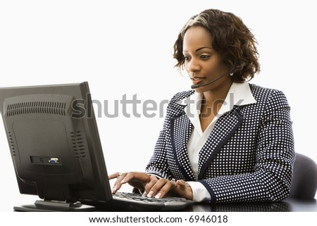 Businesswoman sitting at office desk typing on computer and talking into telephone headset. - stock photo