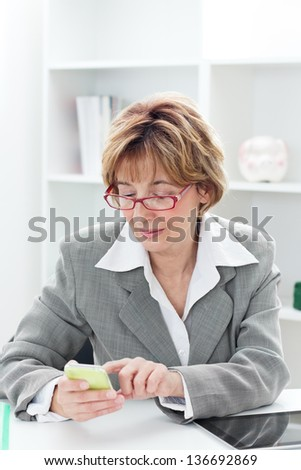 Businesswoman sitting at the table and typing message on the smart phone. - stock photo