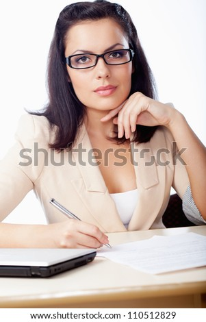 businesswoman sitting behind the desk  and writinig document - stock photo