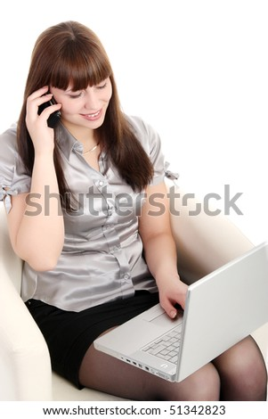 Businesswoman sitting in a chair with a laptop and talking on a mobile phone