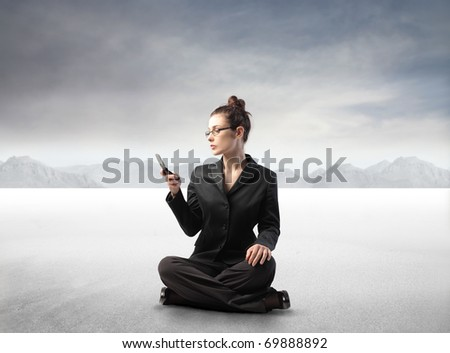 Businesswoman sitting in a desert and using a mobile phone