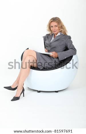Businesswoman sitting in a funky chair with a laptop - stock photo