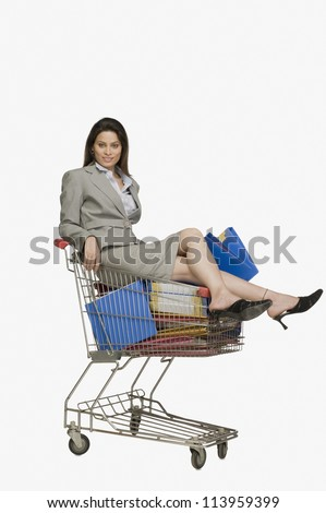 Businesswoman sitting in a shopping cart with files