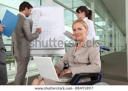 Businesswoman sitting in a wheelchair during a presentation - stock photo