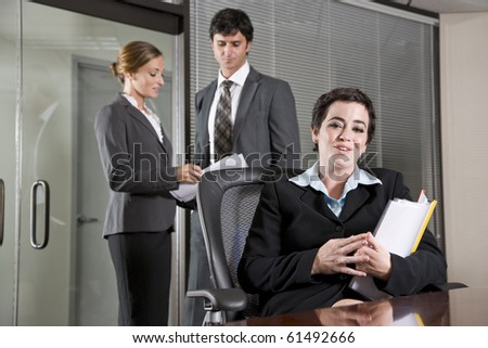 Businesswoman sitting in boardroom, co-workers discussing paperwork in background