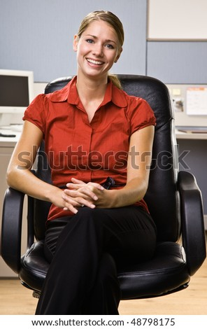 Businesswoman sitting in chair smiling