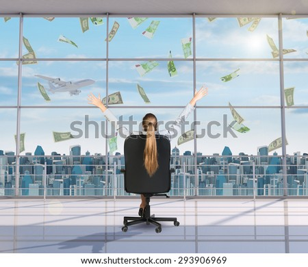 Businesswoman sitting in chair with arms up and looking at money through window, rear view