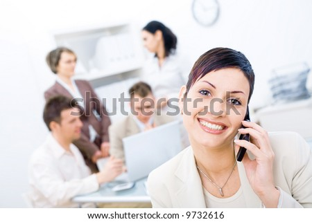 Businesswoman sitting in front, calling on phone, looking at camera, smiling. Four business colleagues working on laptop computer in background. - stock photo