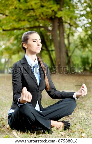 businesswoman sitting in lotus position on grass in park - stock photo