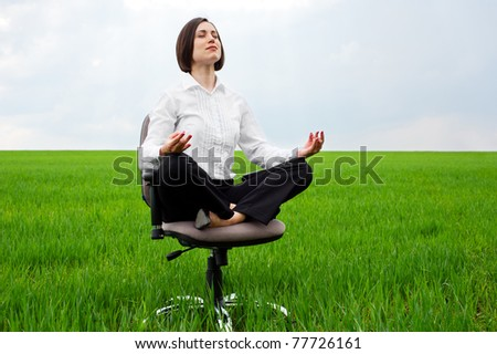 businesswoman sitting in lotus position on green field - stock photo