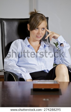 Businesswoman sitting in office, smiling