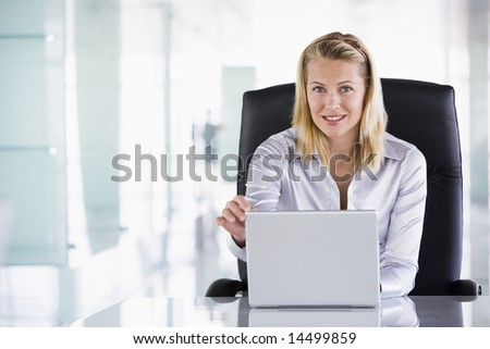 Businesswoman sitting in office with laptop smiling - stock photo