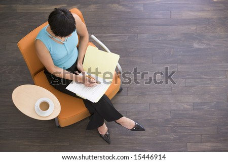 Businesswoman sitting indoors with coffee and folder - stock photo
