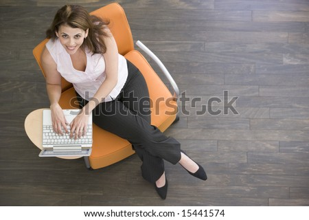 Businesswoman sitting indoors with laptop smiling - stock photo
