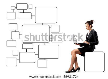 Businesswoman sitting on a cell of a graphic and using a laptop