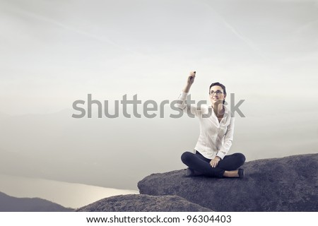 Businesswoman sitting on a rock over a lake and writing - stock photo