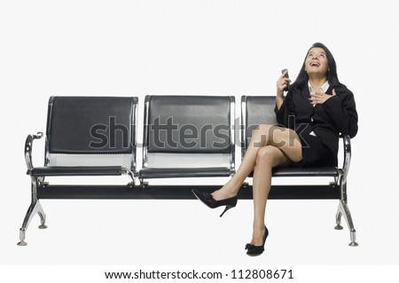 Businesswoman sitting on an armchair and looking up with excitement