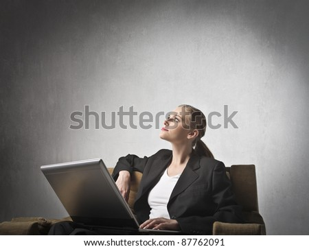 Businesswoman sitting on an armchair and using a laptop - stock photo