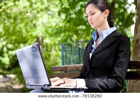 businesswoman sitting on bench in park and working - stock photo