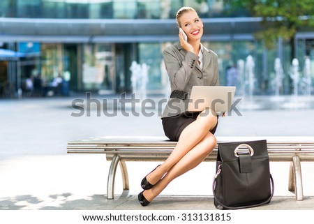 Businesswoman sitting on bench outdoors