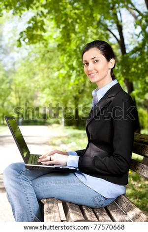businesswoman sitting on bench working on laptop in park - stock photo