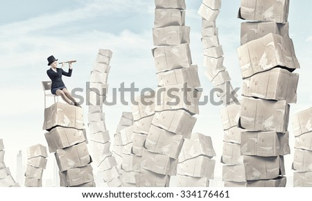 Businesswoman sitting on big stack of carton boxes and looking in spyglass - stock photo