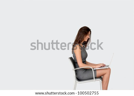 Businesswoman sitting on chair in front of laptop - stock photo