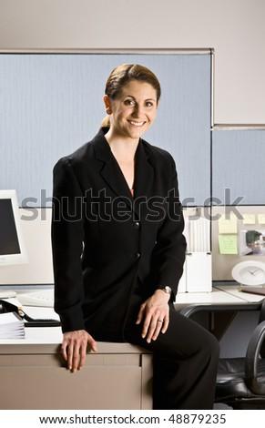 Businesswoman sitting on desk - stock photo