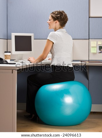 Businesswoman sitting on exercise ball at desk - stock photo