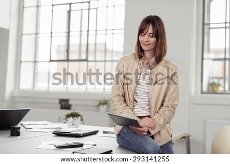 Businesswoman sitting on her desk in the office using a tablet computer reading information on the screen with a smile - stock photo