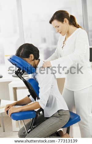 Businesswoman sitting on massage chair, getting back massage.? - stock photo