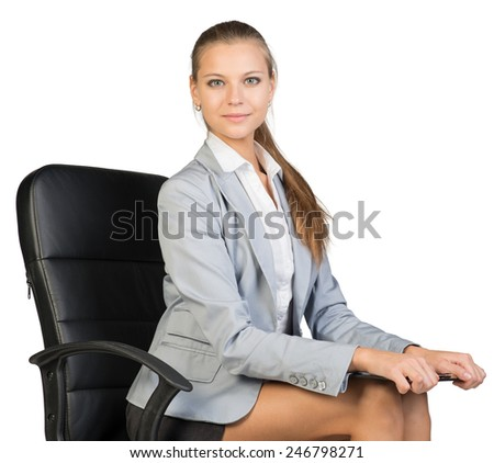 Businesswoman sitting on office chair holding clipboard on her knees, looking at camera. Isolated over white background - stock photo