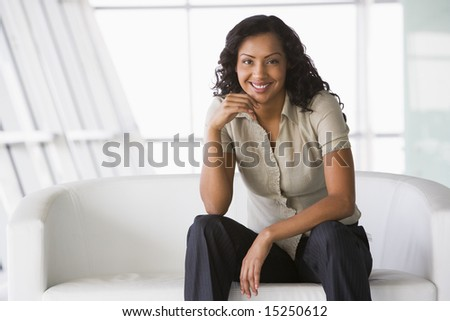 Businesswoman sitting on sofa in office lobby - stock photo
