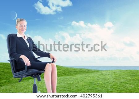 Businesswoman sitting on swivel chair in black suit against green field under blue sky