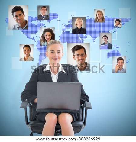 Businesswoman sitting on swivel chair with laptop against blue background