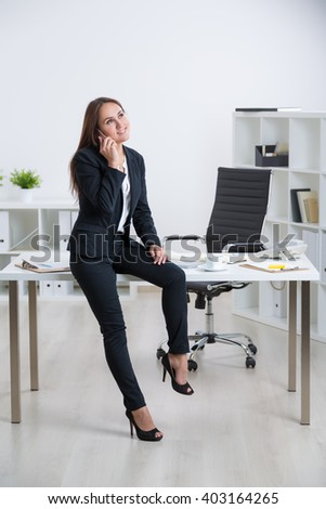 Businesswoman sitting on table, talking on the phone in office interior - stock photo