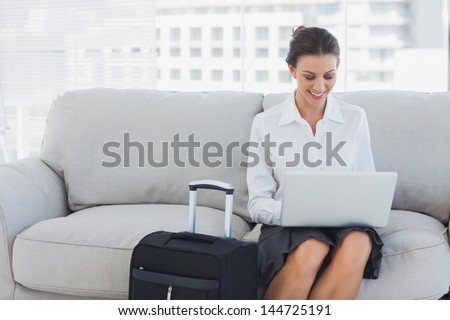 Businesswoman sitting on the couch using laptop beside her suitcase - stock photo