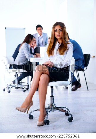 Businesswoman sitting on the office chair in front of business meeting - stock photo